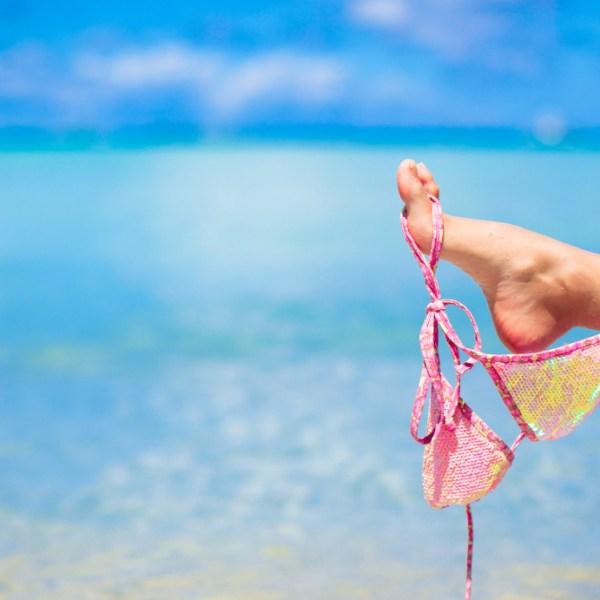 Pink swimsuit on female leg on white tropical beach_308934