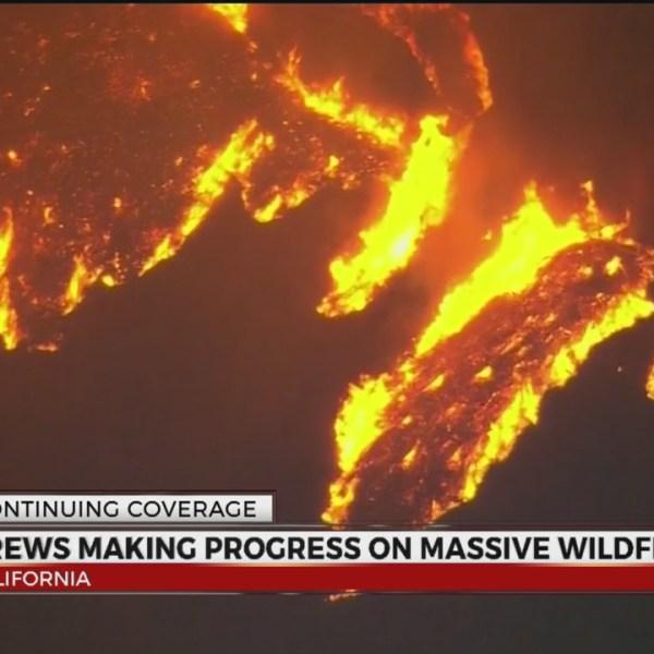 Crews make progress progress on massive wildfires
