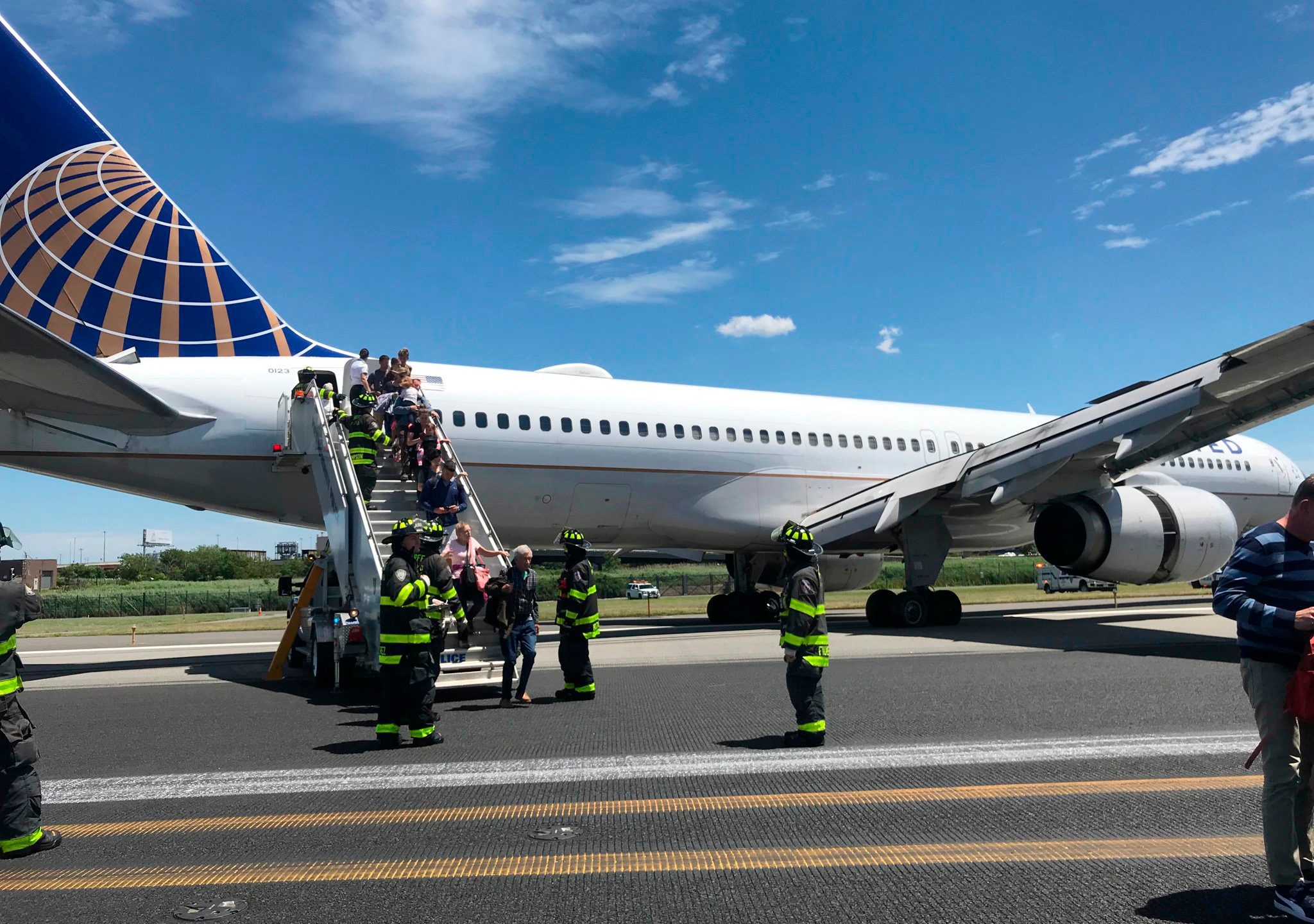 Emergency personnel help passengers off a plane after a United Airlines plane skidded off the runway after landing at Newark Liberty International Airport on Saturday, June 15, 2019 in Newark, N.J.