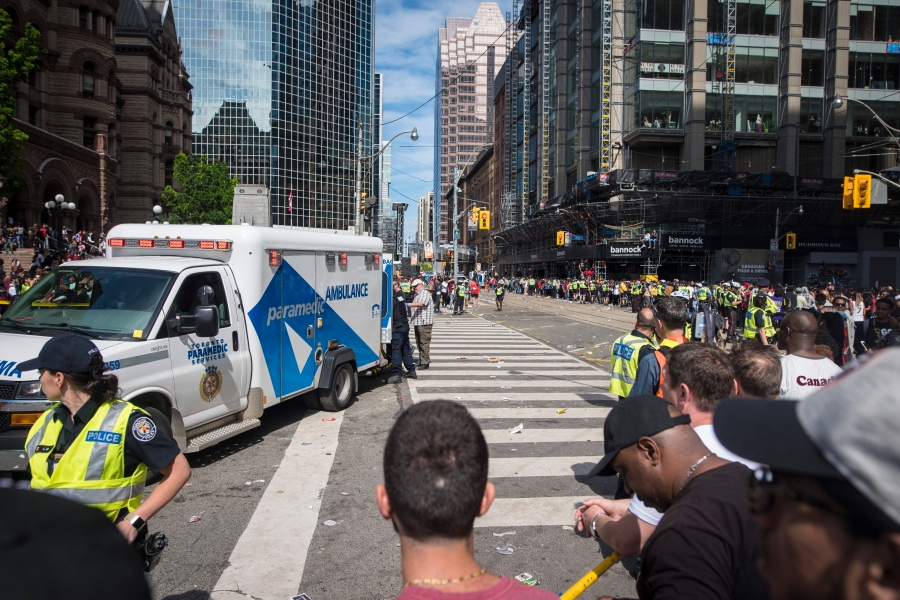 An ambulance arrives to the scene after shots were fired during the Toronto Raptors NBA basketball championship victory celebration near Nathan Phillips Square in Toronto, Monday, June 17, 2019.
